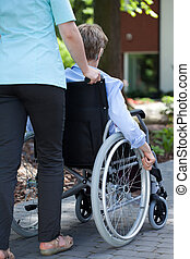 Nurse walking with elderly woman on wheelchair - Close-up of...