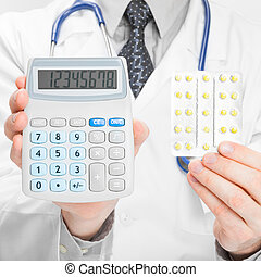 Doctor holdling calculator and pills in his hands - heath...