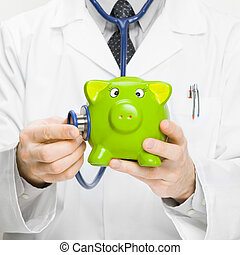 Doctor holding stethoscope and piggybank in hand - 1 to 1...