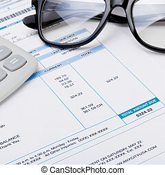 Studio shot of calculator and glasses over some receipt - 1...
