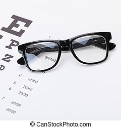 Table for eyesight test with glasses over it - studio shot -...