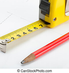 Tape measure with pencil above blueprint - 1 to 1 ratio