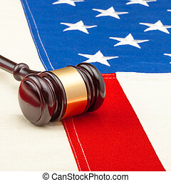 Wooden judge gavel over US flag - closeup studio shot - 1 to...