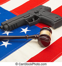 Wooden judge gavel and gun over USA flag - studio shoot - 1...