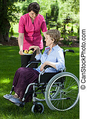 Caregiver giving pear to disabled senior woman - Caregiver...