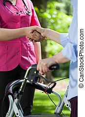 Doctor shaking hands with patient outdoors - Close-up of...