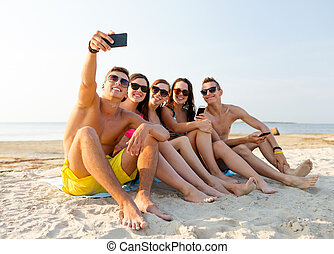 friends with smartphones on beach - friendship, leisure,...