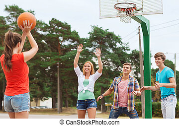 group of smiling teenagers playing basketball - summer...