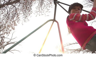 Spring Swing - Two children ride on a swing Sun - backlight...