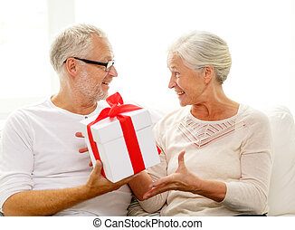 happy senior couple with gift box at home - family,...