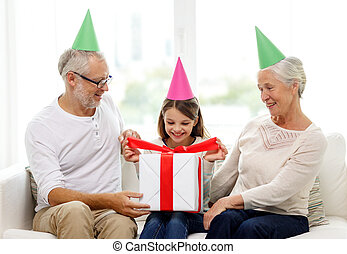 smiling family in party hats with gift box at home - family,...