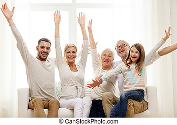 happy family sitting on sofa at home - family, happiness,...