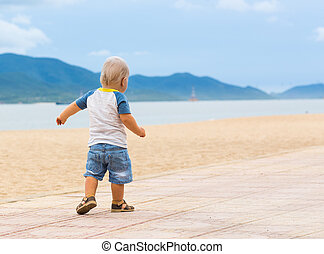 Baby walking along the beach