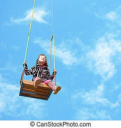 Girl on a swing - happy little girl on a swing on sky...