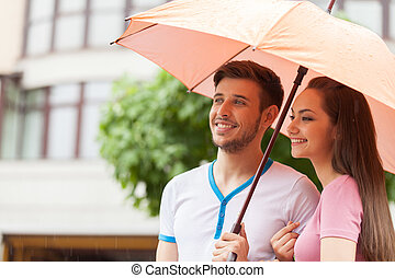 Portrait of woman and man standing under umbrella beautiful...