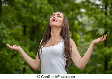 Happy young woman enjoying rain in summer Woman standing...