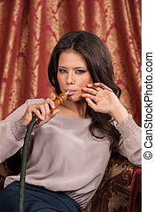 Beautiful young woman inhaling hookah. girl smoking turkish...