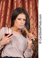 Beautiful young woman exhaling hookah. girl smoking turkish...