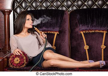 Beautiful young woman inhaling hookah. girl smoking shisha lying on sofa in cafe