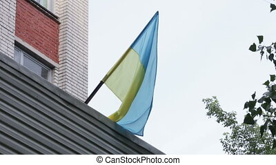 Ukrainian flag in city - On roof building hangs Ukrainian...
