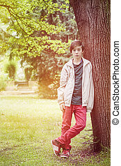 teenager boy leaning against a tree in a park