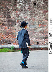 Young Orthodox Jew walking in the street - MILAN, ITALY -...
