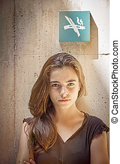 strictly looking teenager girl with no smoking sign on the wall
