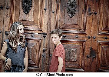 portrait of two teenager in front of a huge ancient wooden door