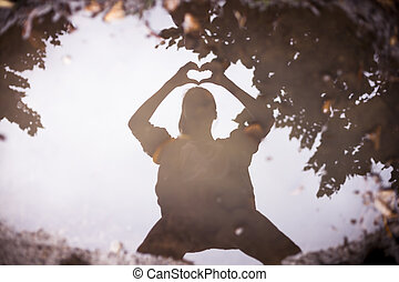 reflection in a puddle of a person who shapes a heart with...