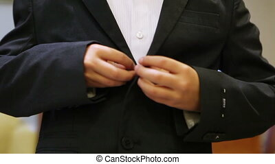 Fastening buttons on jacket - Child wears a jacket and...