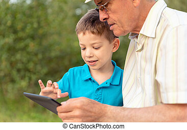 Grandchild and grandfather using a tablet outdoors - Closeup...