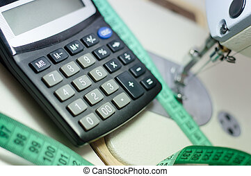 close up picture of calculator at white sewing machine and...