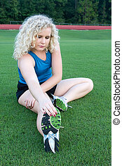 Coed Stretching - A pretty coed does warmup stretches in the...
