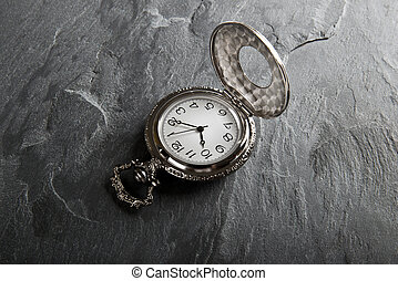 Pocket gray clock on dark gray slate texture