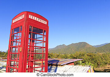 Old-fashioned traditional red telephone booth or public payphone