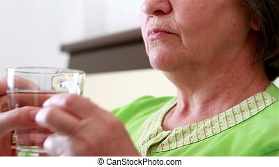 Senior woman taking a pill - Close up of senior woman taking...