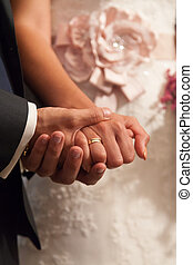 Wedding hands - Bride and groom holding hands during the...