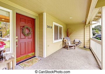 Spacious entrance porch with red door and wooden chair