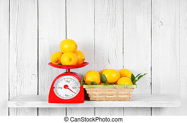 Lemons on scales and in a basket on a wooden shelf.