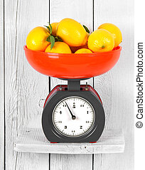 Lemons on scales on a wooden shelf