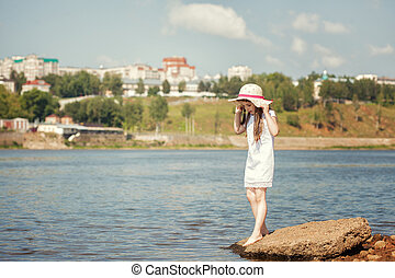 Little fashionista walks along river in park - Image of...