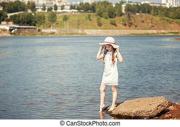 Curious little girl walking along river bank - Image of...