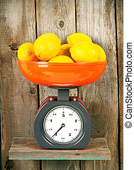 Lemons on scales on a wooden shelf.