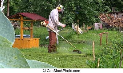 Gardener cut grass - Gardener man cut grass with trimmer...