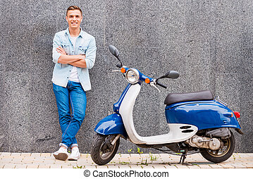 Me and my new scooter. Handsome young man leaning at the...