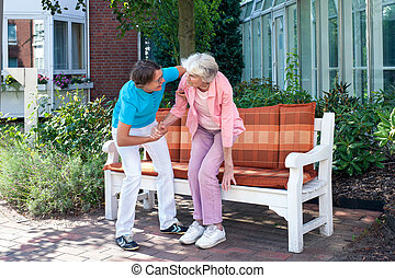 Care assistant tending to a senior lady helping her to make...