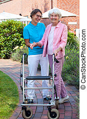 Care assistant helping an elderly lady as they take a walk...