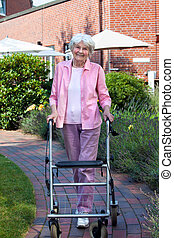Happy elderly woman using a walking aid standing on a paved...