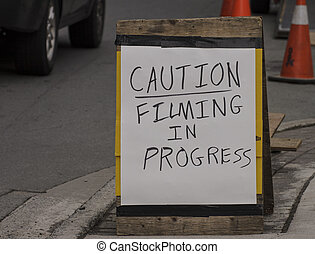Caution sign - A sign warns traffic of a film production...
