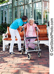 Senior woman being helped by a care assistant to rise from a...